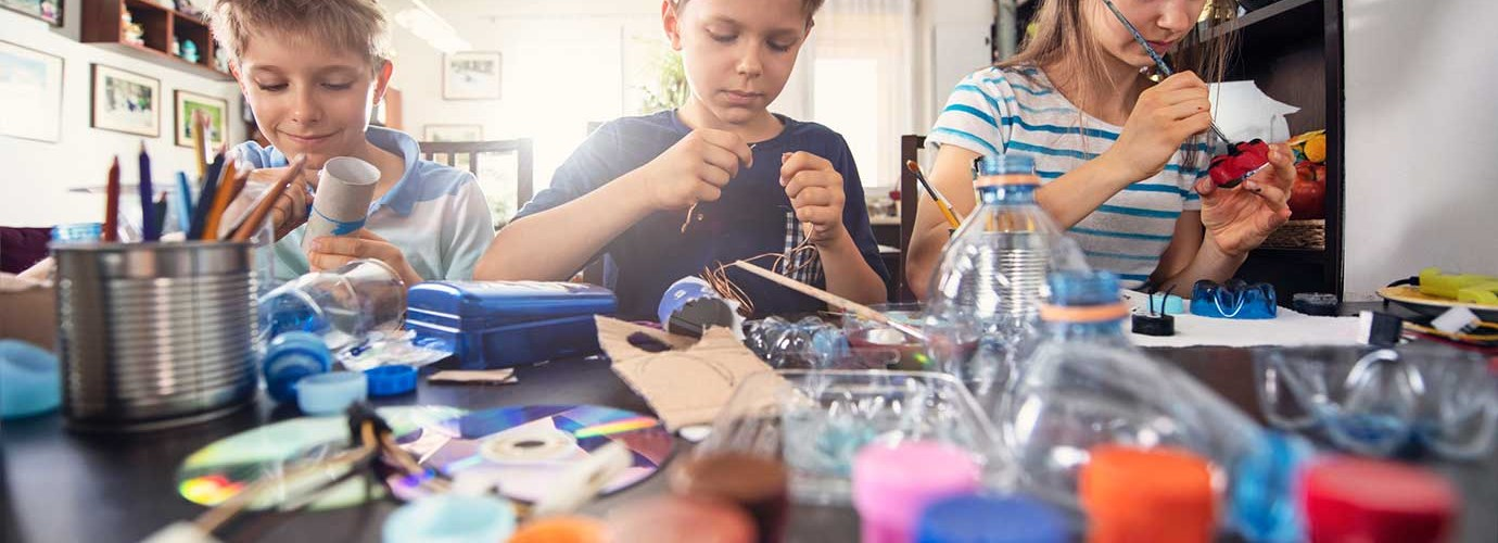 3 children learning how to reduce waste by making crafts from recyclable plastics and cardboard tubes