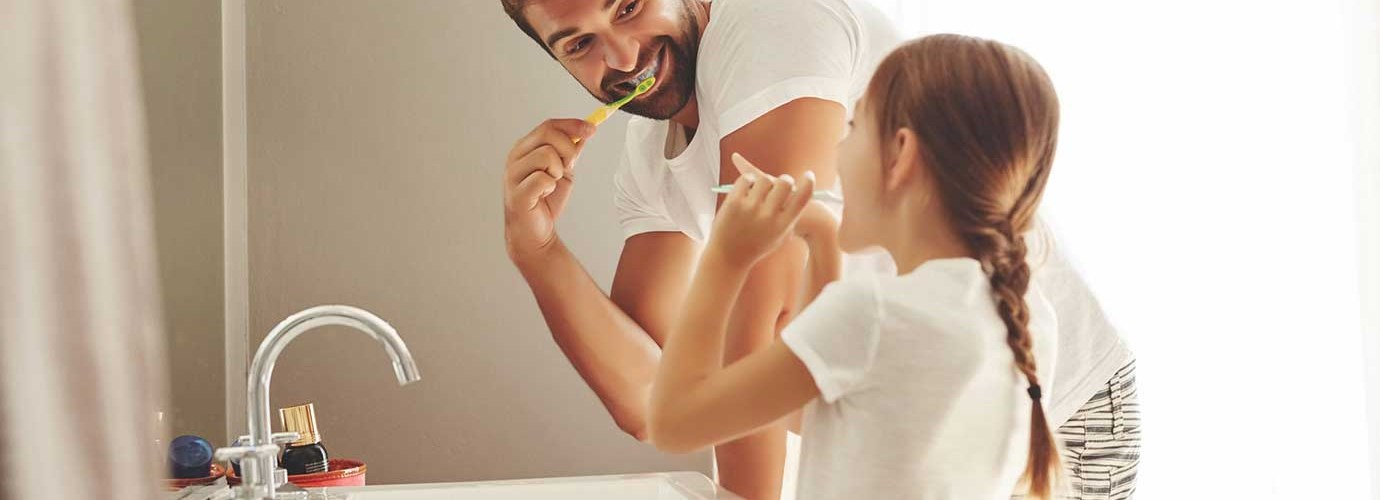 A man and his young daughter learning how to save water whilst brushing their teeth together in a bathroom