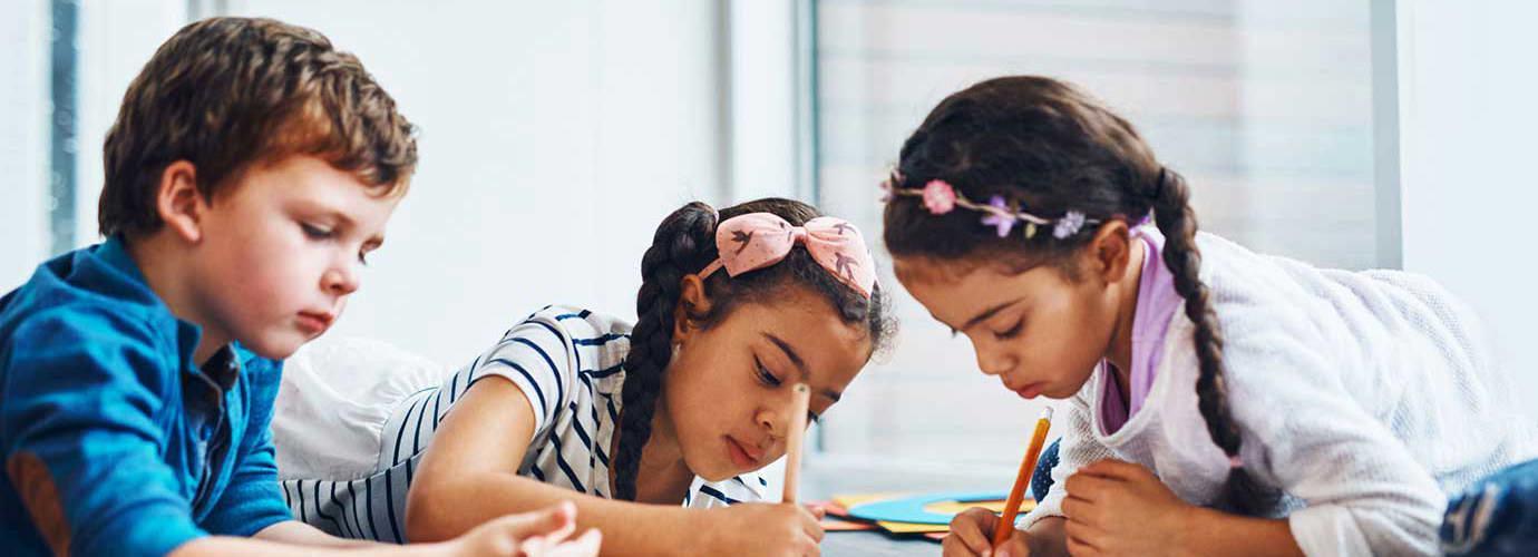 Drie kinderen tekenen met kleurrijk potlood terwijl ze op de vloer liggen