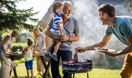 Man bereidt een barbecue voor in de achtertuin van het gezin