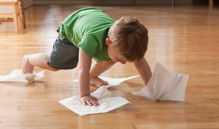 Kind maakt de vloer schoon met keukenpapier