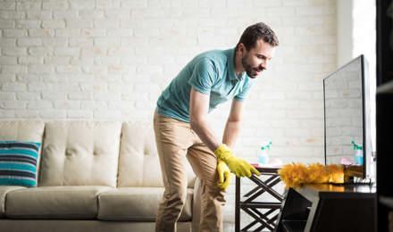 Man stoft zijn huis af met een stofdoek