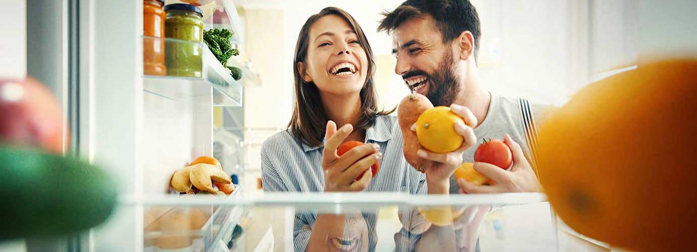 Een stel haalt wat fruit en groenten uit de koelkast