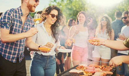 Een groep van vrienden staan op een bbq-feest rondom een bbq-grill