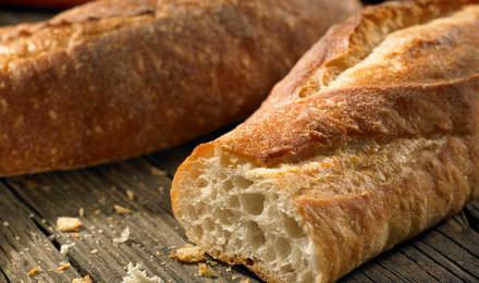 Een gesneden stokbrood met kruimels op een verweerde houten tafel