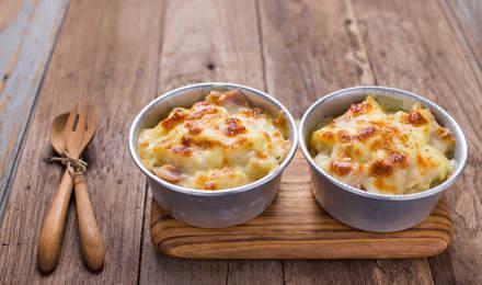 Twee kommen geraspte kaas staan op een snijplank met een mes en vork ernaast op een houten tafel