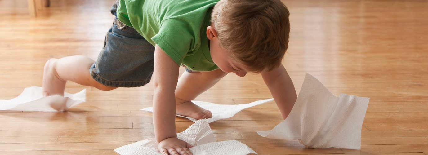 Kid cleaning the floor with paper towels