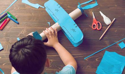 Kind bouwt een doet-het-zelf kartonnen vliegtuigje