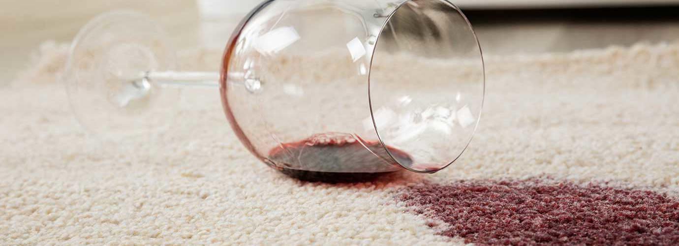 Wijnglas omgevallen op een crème tapijt vormt een wijnvlek