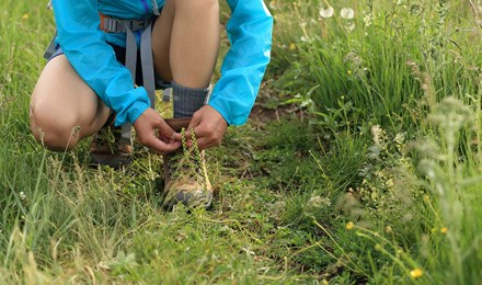 Kind strikt de veters van zijn wandelschoenen buiten