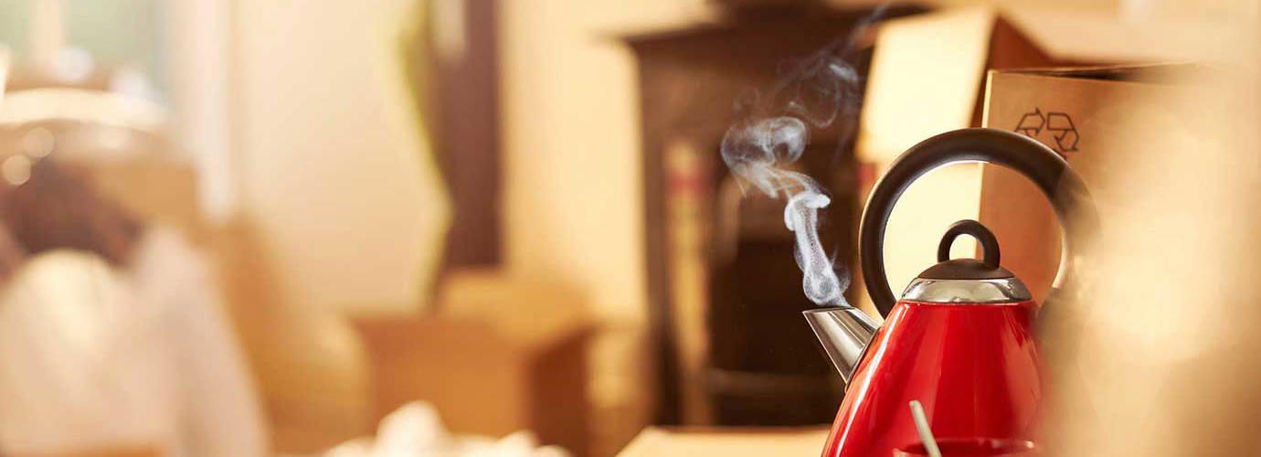 Ein roter Wasserkocher steht auf einer Kückenfläche und kocht