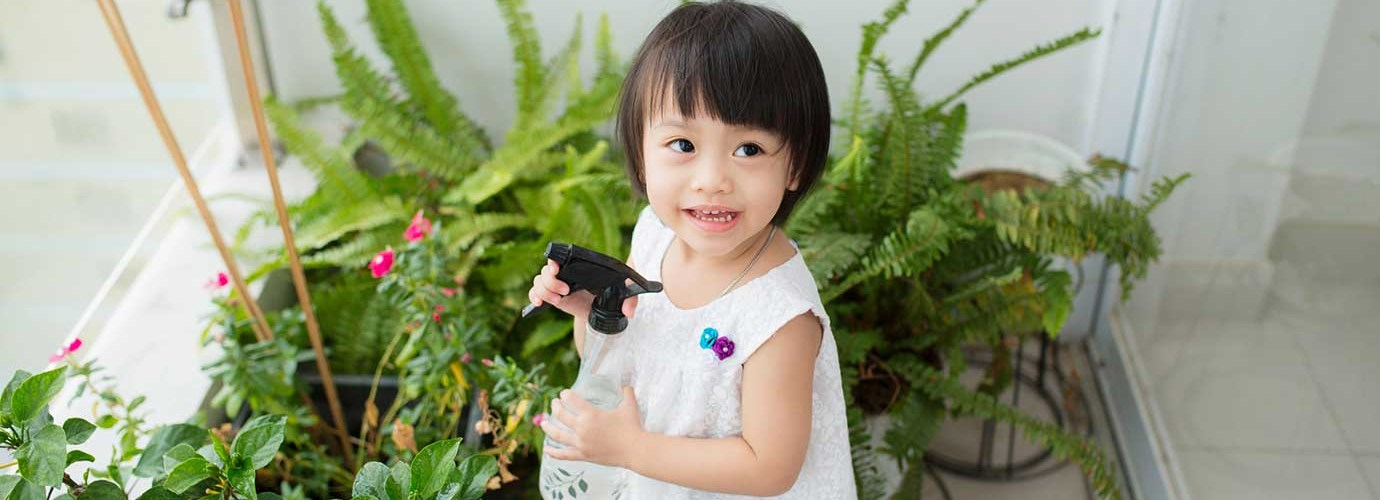Little girl taking care of indoor plants